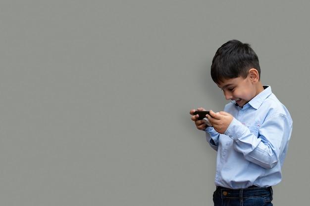 Vrije tijd, kinderen, technologie en mensenconcept - lachende jongen met smartphone of thuis een spel spelen