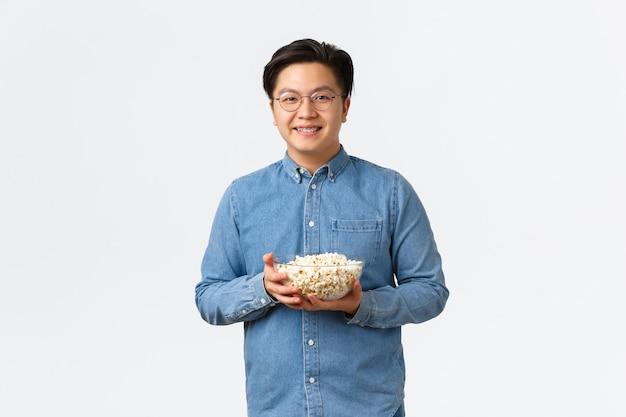 Vrije tijd, levensstijl en mensenconcept. bescheiden schattige aziatische man met beugel en bril met popcorn en lachend, klaar om premier op tv te kijken, staande witte muur.