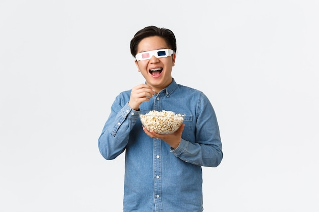 Vrije tijd, levensstijl en mensenconcept. vrolijke lachende aziatische man in 3d-bril, popcorn eten en