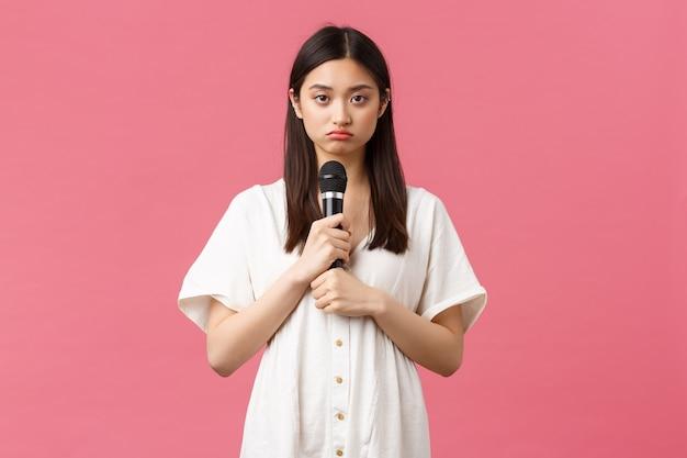 Vrije tijd, mensen emoties en lifestyle concept. somber en terughoudend jong aziatisch meisje dat microfoon vasthoudt en een droevige camera kijkt, niet bereid om op te treden, staande humeurige roze achtergrond.