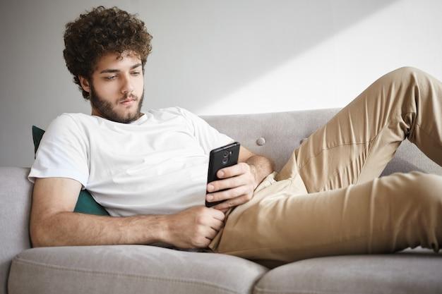Vrije tijd, technologie en communicatieconcept. coole ongeschoren man met volumineus golvend kapsel liggend op de bank in zijn moderne appartement online pizza bestellen op zijn elektronische apparaat
