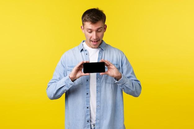 Vrije tijd technologie en toepassing advertentie concept gelukkig onder de indruk mannelijke student knappe jongen smartphone weergegeven: mobiele scherm en kijken verbaasd