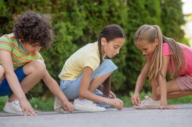 Vrije tijd, tekening. twee langharige meisjes en een jongen met krullend haar in lichte vrijetijdskleding tekenen op asfalt in de frisse lucht