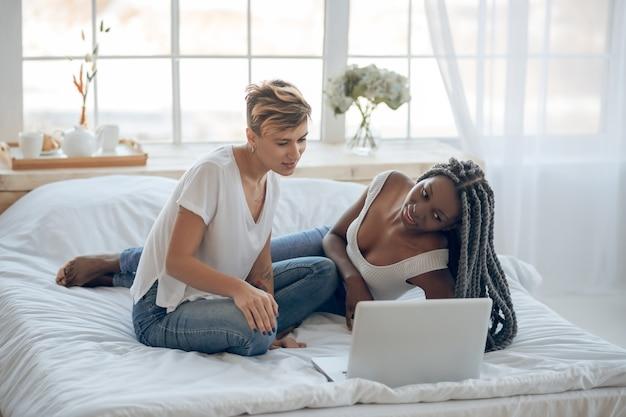 Vrije tijd. twee meisjes kijken naar een film op een laptop en voelen zich positief