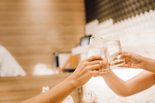 Vrije tijd, vakantie, eten, mensen en eten concept - vrienden eten in het restaurant en rammelende drankjes
