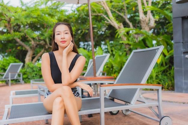 Vrije tijd van de portret ontspant de mooie jonge aziatische vrouw glimlach rond openluchtzwembad voor vakantie