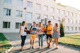 Vrije tijd van een student, bachelor campus levensritme. Vijf vriendelijke studenten lopen
