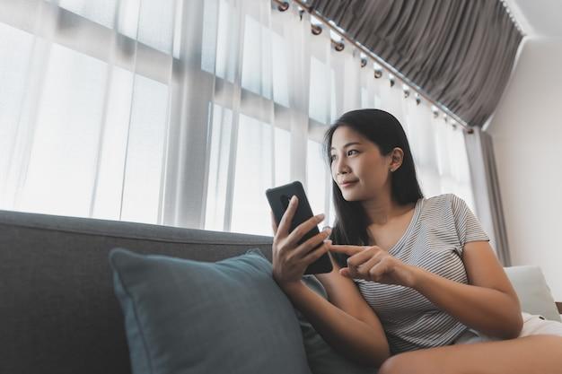 Vrije tijd vanuit huis en online winkelconcept, gelukkige aziatische vrouw ontspant en gebruikt mobiele telefoon op de bank in de woonkamer thuis
