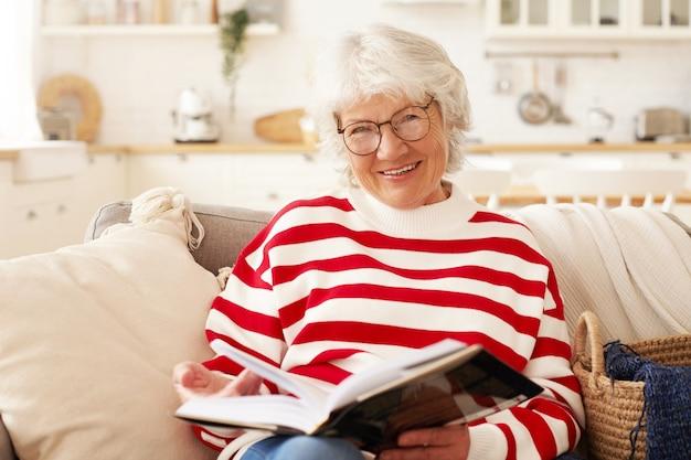 Vrije tijd, zelfstudie, hobby en pensioenconcept. foto van knappe volwassen senior vrouw in gestreepte trui en stijlvolle brillen genieten van lezen in de woonkamer, glimlachend vreugdevol
