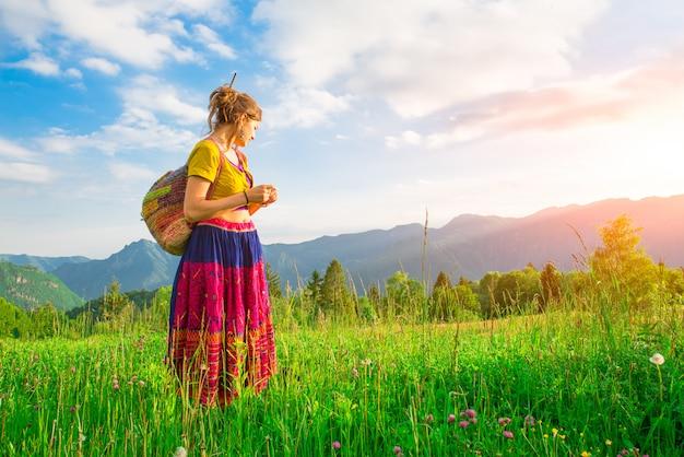 Vrije toevallige vrouw in aard in de bergen in de de lenteweide