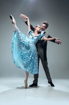 Vrije vlucht. mooie eigentijdse balzaaldansers die op grijze muur worden geïsoleerd. sensuele professionele artiesten die walz, tango, slowfox en quickstep dansen. flexibel en gewichtloos.