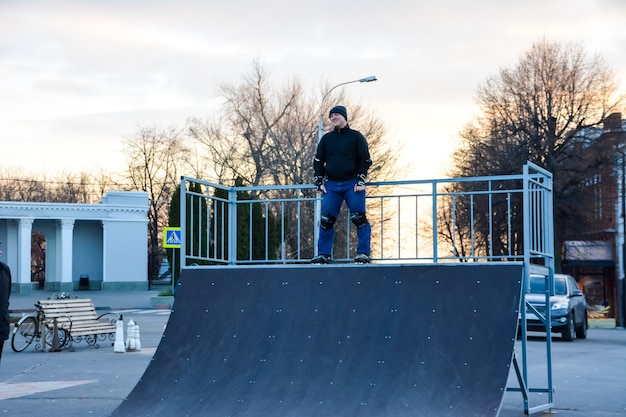 Vrijetijdsbesteding man rolschaatsen in het centrum van de stad op de zonsondergang. winter. straat rolschaatsen.