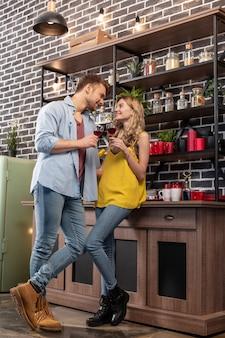 Vrijetijdskleding. net getrouwd stel in stijlvolle vrijetijdskleding die thuis wijn drinkt terwijl ze romantische tijd doorbrengt