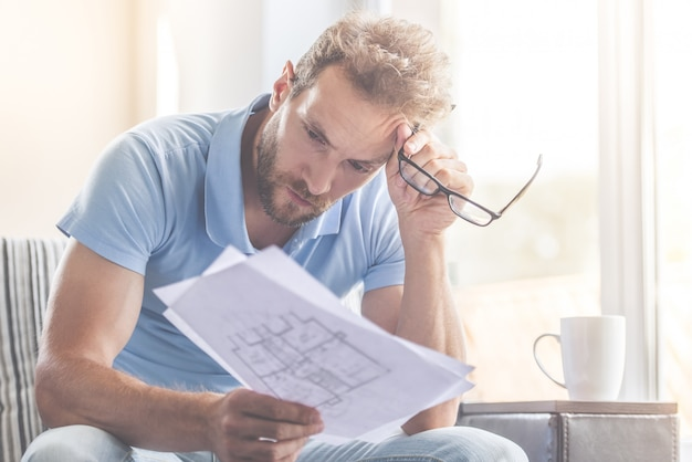 Vrijetijdskleding onderzoekt documenten en houdt een bril vast
