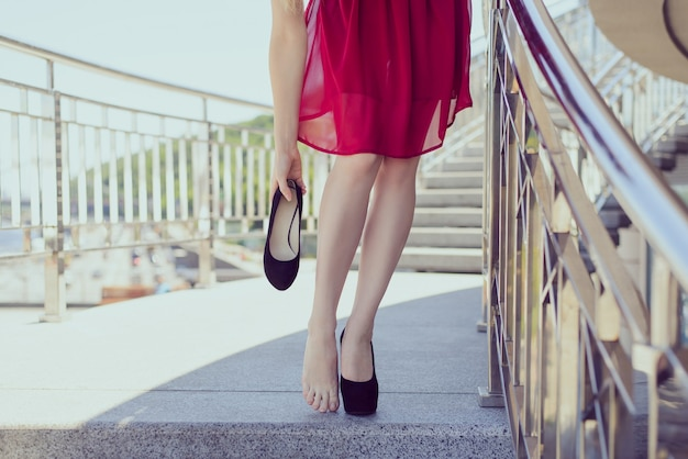 Vrijheid comfort schoenen accessoires concept. close-up foto van klassieke kersen kleur bordeaux kastanjebruine cocktail avondjurk, hand schoenen, ideale perfecte benen, stiletto's, pumps, prom