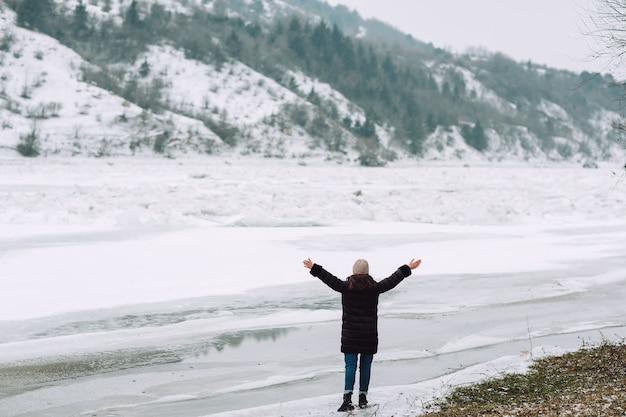 Vrijheid en gelukkig wintertijdconcept. gelukkig meisje dat haar handen op de bevroren rivier op aard opheft.
