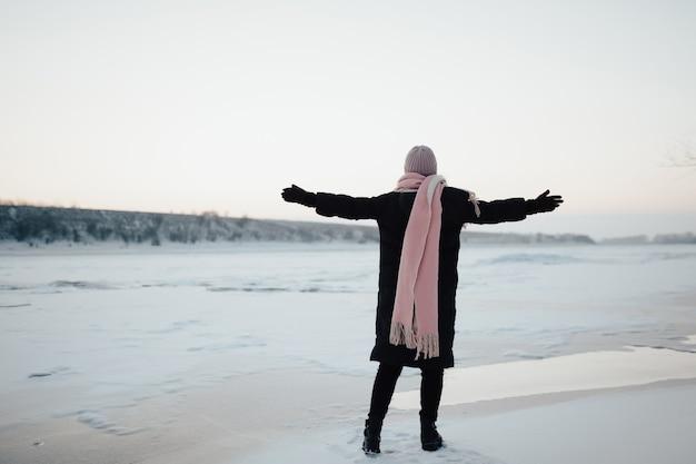 Vrijheid en gelukkige wintertijd. gelukkig meisje dat haar handen op de bevroren rivier op aard opheft.