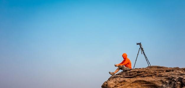 Vrijheid fotografie stock afbeeldingen zittend en camera statief op berg rots op sam phan bok ubon ratchathani thailand geïsoleerde blauwe hemelachtergrond