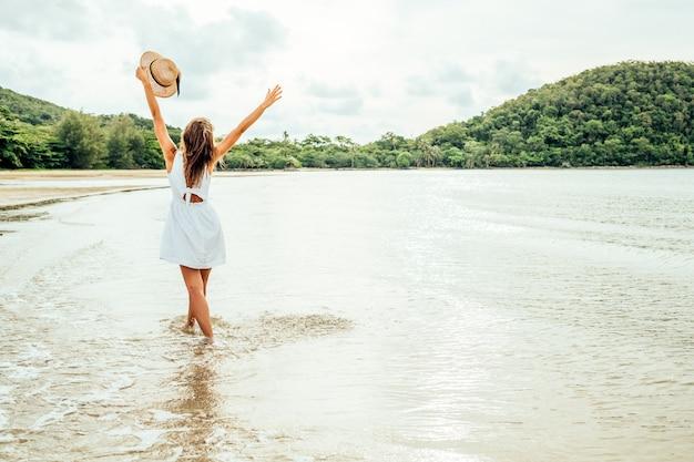 Vrijheid gelukkige vrouw met opgeheven armen op het strand op een zonnige dag