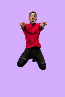Vrijheid in beweging en voorwaartse beweging. de blij verraste jonge afrikaanse man die tegen een blauwe studioachtergrond springt runnin man in beweging of beweging. menselijke emoties en gezichtsuitdrukkingen