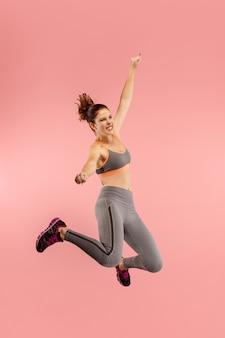 Vrijheid in beweging. in de lucht schot van vrij gelukkige jonge vrouw die en tegen oranje studioachtergrond springt gebaren. runnin meisje in beweging of beweging