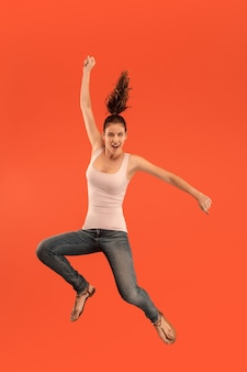 Vrijheid in beweging. in de lucht schot van vrij gelukkige jonge vrouw springen en gebaren tegen oranje studio achtergrond. menselijke emoties en gezichtsuitdrukkingen concept