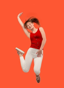 Vrijheid in beweging. in de lucht schot van vrij gelukkige jonge vrouw springen en gebaren tegen oranje studio achtergrond. runnin meisje in beweging of beweging. menselijke emoties en gezichtsuitdrukkingen concept