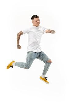 Vrijheid in beweging. knappe jonge man springen tegen een witte achtergrond