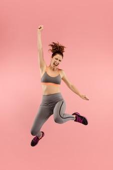 Vrijheid in beweging. vrij jonge vrouw die tegen oranje achtergrond springt