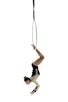 Vrijheid. jonge acrobaat, circusatleet die op witte studioachtergrond wordt geïsoleerd. perfect gebalanceerde training tijdens de vlucht, ritmische gymnastiekartiest die oefent met apparatuur. genade in prestaties.
