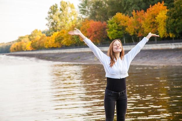 Vrijheid. jonge mooie vrouw in het herfstpark in de buurt van het meer. buitenopname