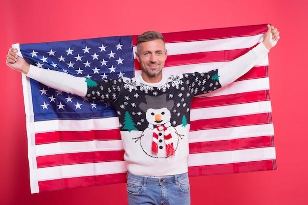 Vrijheid voor altijd. knappe man vieren wintervakantie rode achtergrond. guy draagt wintertrui. vrolijk kerstfeest en een gelukkig nieuwjaar. beste wensen. winter vakantie. volwassen man houdt amerikaanse vlag vast.