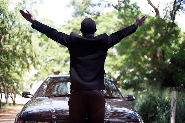 Vrijheids afrikaanse zakenman in kostuum die zich dichtbij auto met groene natuurlijke achtergrond bevinden.