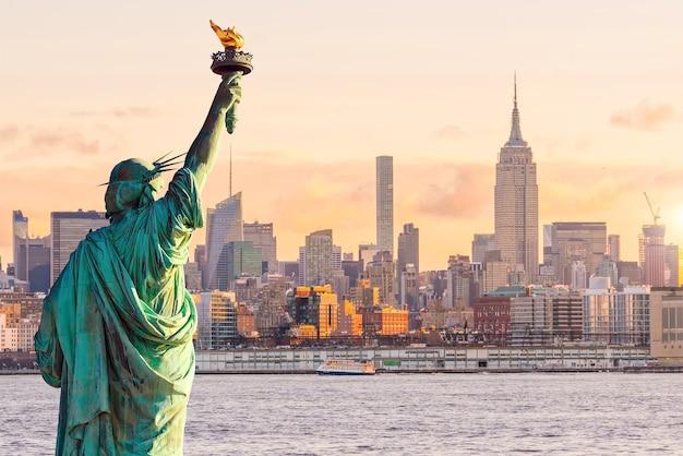 Vrijheidsbeeld en de skyline van new york bij zonsondergang, in de verenigde staten