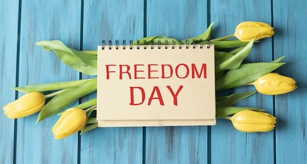 Vrijheidsdagtekst op blocnote die op houten achtergrond bloeien
