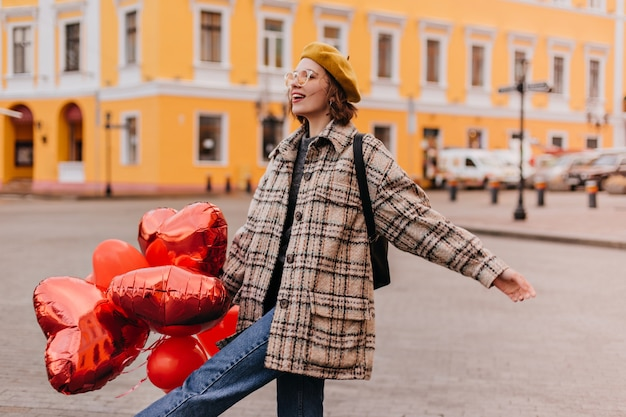 Vrijheidslievende vrouw in spijkerbroek en gele baret geniet van een wandeling door de stad
