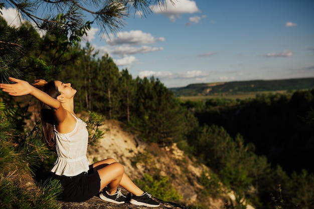 Vrijheidsmeisje met handen omhoog in de bergen. ze voelt zich sterk en zelfverzekerd.
