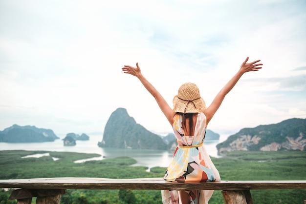Vrijheidsreiziger vrouw ontspannen met opgeheven armen op de top van de berg