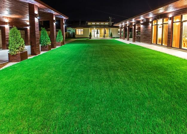 Vrijstaande luxe woning 's nachts - uitzicht vanaf buiten de binnenplaats met een groen gazon.