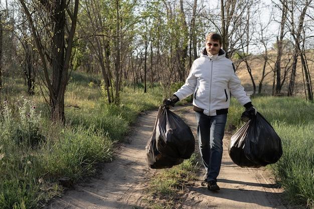 Vrijwillige man houdt twee grote zwarte zakken vast, een deel van de afvalinzameling in het park. langs de weg lopen en afval vervoeren
