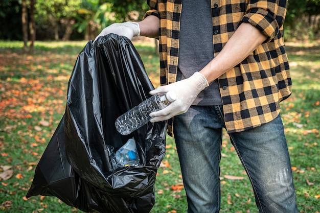 Vrijwillige man in handschoenen om plastic fles op te pakken in plastic zwarte zak om het park schoon te maken tijdens milieuactiviteiten om afval te verzamelen