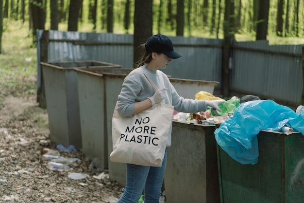 Vrijwillige vrouw wordt gereinigd in het bos vrouw verzamelt plastic