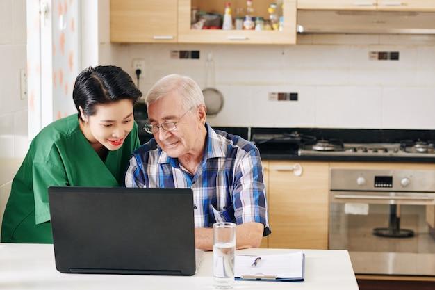 Vrijwilliger die hogere mens toont hoe laptop te gebruiken