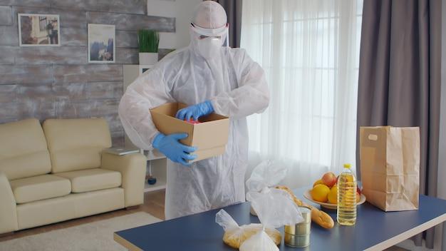 Vrijwilliger die voedsel organiseert met een beschermend pak tijdens de covid-pandemie.