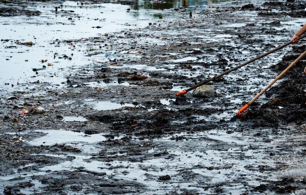 Vrijwilliger gebruikt de hark om het afval uit de zee te vegen. strandreiniger die afval op het overzeese strand verzamelt. vuilnis op het strand opruimen. strand milieuvervuiling. plastic op vuile kust.