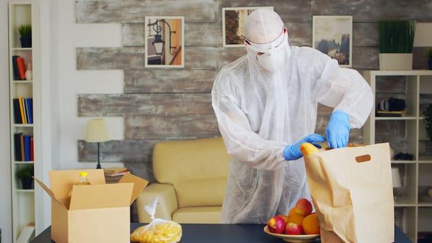 Vrijwilliger in beschermingspak voedsel inpakken tijdens covid quarantaine.