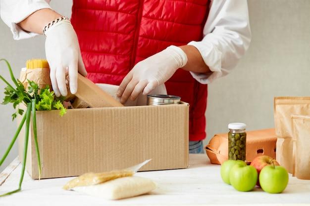 Vrijwilliger in het beschermende medische masker en handschoenen eten in donatiebox. levering man werknemer in rood vest verpakking met voedsel. service quarantaine pandemisch coronavirus.