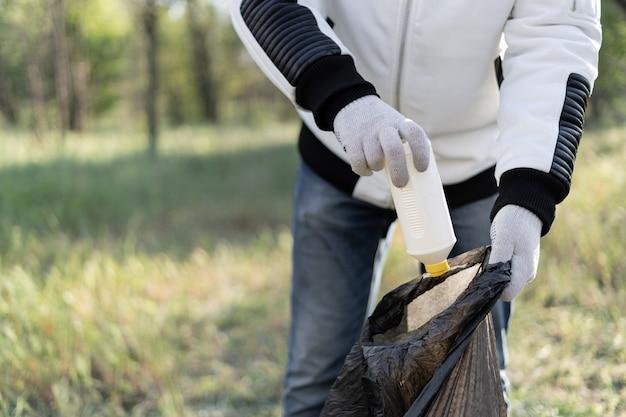 Vrijwilliger maakt het park schoon van verspreid puin en verzamelt het in een zak. ecologie, milieubescherming concept.