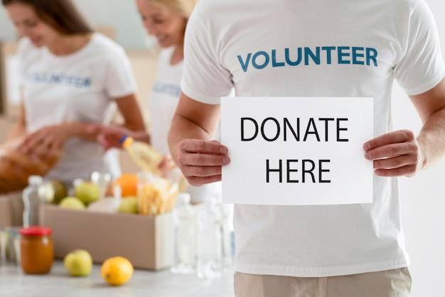 Vrijwilliger met aanplakbiljet met instructies voor donatie