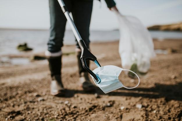 Vrijwilliger strandopruiming haalt gezichtsmasker op voor milieucampagne